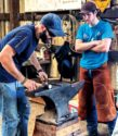 A farrier works on a shoe with an anvil.